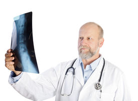 stock photo of x-files  - Serious doctor is holding an vertebrae X - JPG