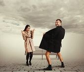 funny picture of laughing woman and crazy exhibitionist in coat