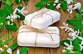 foto of honeysuckle  - Two bars of soap white tied with twine twigs with leaves and white flowers of honeysuckle on a background of wooden boards - JPG