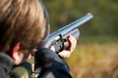stock photo of rifle  - Shooter takes aim for a shot from rifle
