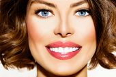 Healthy Smile. Teeth Whitening. Beautiful Smiling Young Woman Portrait close up. Over White backgrou