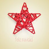 a red christmas star and the sentence feliz navidad, merry christmas written in spanish, on a beige