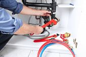 picture of clog  - Hands of professional Plumber with a wrench - JPG
