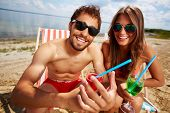 picture of beach party  - Relaxed young lovers partying on the beach on a sunny day - JPG
