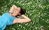 picture of lie  - Female athlete resting and relaxing after workout. Woman lying down on grass and spring flowers. Healthy lifestyle and happiness concept.