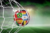 stock photo of football  - Football in multi national colours at back of net against football pitch under green sky and spotlights - JPG