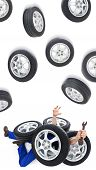 picture of overwhelming  - Car mechanic on the flor covered with tires  - JPG