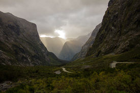 stock photo of twisty  - The twisty road to Milford Sound cloudy sky sun just breaking through.  ** Note: Visible grain at 100%, best at smaller sizes ** Note: Soft Focus at 100%, best at smaller sizes - JPG