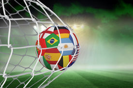 stock photo of football pitch  - Football in multi national colours at back of net against football pitch under green sky and spotlights - JPG