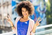 foto of peace-sign  - Afro woman giving a peace sign  - JPG