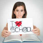image of hate  - Girl studying and holding a sign with the words I hate school - JPG