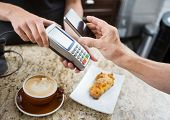 stock photo of over counter  - Cropped image of customer paying through mobilephone over electronic reader at cafe counter - JPG