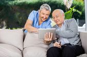 pic of male nurses  - Male caretaker and senior man using tablet PC at nursing home porch - JPG