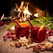image of christmas spices  - Two glasses of  mulled wine with christmas decoration at romantic fireplace - JPG