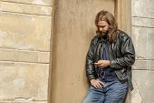 stock photo of long beard  - Blond long hair and beard young adult hipster man listening music. Outdoor urban scene. ** Note: Soft Focus at 100%, best at smaller sizes - JPG