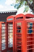stock photo of phone-booth  - Two old red phone booths in a park - JPG