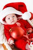 image of new years baby  - Cute newborn baby wearing Santa Claus hat sleeping in basket - JPG
