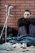 stock photo of homeless  - Ill homeless young man sitting on the ground - JPG