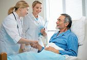 stock photo of congrats  - doctor shakes hands with patient in hospital bed - JPG