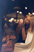 image of night gown  - A woman doing some touch ups on a night out - JPG