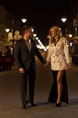 stock photo of night gown  - An elegant couple walking through a city at night - JPG