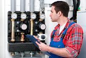 image of hot water  - Technician servicing the gas boiler for hot water and heating - JPG