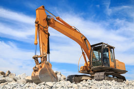 foto of power-shovel  - Yellow excavator at the construction site against blue sky - JPG