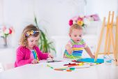 pic of canvas  - Two happy preschool children cute little girl and funny toddler boy painting and drawing together with water color on canvas in a sunny class room with wooden easel creative young artists at work - JPG
