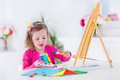 stock photo of little school girl  - Cute happy little girl adorable preschooler painting with water color on canvas standing on a wooden easel in a sunny white room at home or elementary school creative young artist at work - JPG