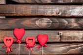pic of sticks  - Four red hearts on sticks on a background of a dark wood - JPG
