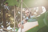 picture of carnival ride  - A father takes his brave daughter on a airplane carnival ride - JPG
