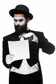 stock photo of mime  - Man with a face mime reading through a magnifying glass isolated on a white background - JPG