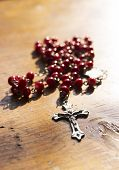 stock photo of rosary  - A rosary with red beads on wooden table - JPG