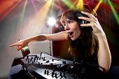 stock photo of emcee  - caucasian female dj using a mixer and computer to play mp3s - JPG