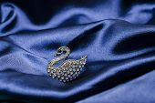 stock photo of brooch  - brooch in the form of a swan on silk waves - JPG