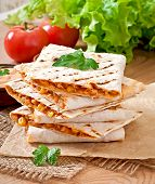 picture of mexican  - Mexican Quesadilla sliced with vegetables and sauces on the table - JPG
