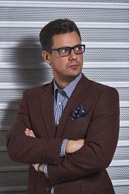stock photo of swagger  - Confident stylish handsome gentleman posing with crossed arms wearing spectacles checked shirt and brown suit jacket with handkerchief in pocket over grey metal textured background - JPG