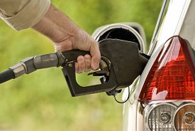 stock photo of fuel pump  - Horizontal close up shot of a hand pumping gasoline or fuel into gas tank on car - JPG