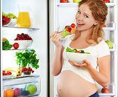 foto of refrigerator  - Happy pregnant woman eating salad near refrigerator at home - JPG