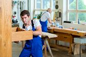 foto of dungarees  - two worker in blue dungarees in a carpenter - JPG