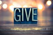 stock photo of tithe  - The word GIVE written in vintage metal letterpress type on a soft backlit background - JPG