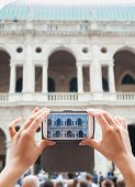 stock photo of vicenza  - Tourist girl using her smartphone to take a photo of the Basilica Palladiana a landmark of Vicenza - JPG
