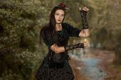 stock photo of gothic girl  - Brunette girl in black dress of gothic style holding a watch on a chain - JPG