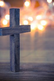 foto of christianity  - A wooden Christian cross with a soft bokeh lights background - JPG