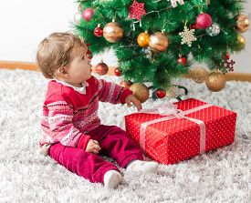 picture of new years baby  - Adorable baby with Christmas gift and winter tree with New Year decoration at home - JPG