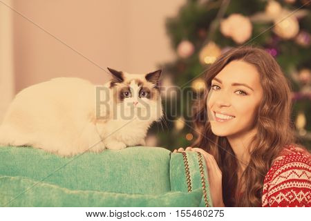 Christmas party, winter holidays woman with cat. New year girl. christmas tree in interior backgroun