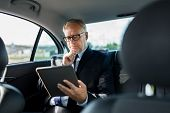 transport, business trip, technology and people concept - senior businessman with tablet pc computer poster