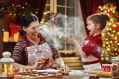 Merry Christmas and Happy Holidays. Family preparation holiday food. Mother and daughter cooking Chr poster