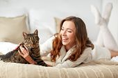 pets, comfort, rest and people concept - happy young woman with cat lying in bed at home poster