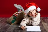 Постер, плакат: Adorable Little Girl Wearing Santa Hat Writing Santa Letter